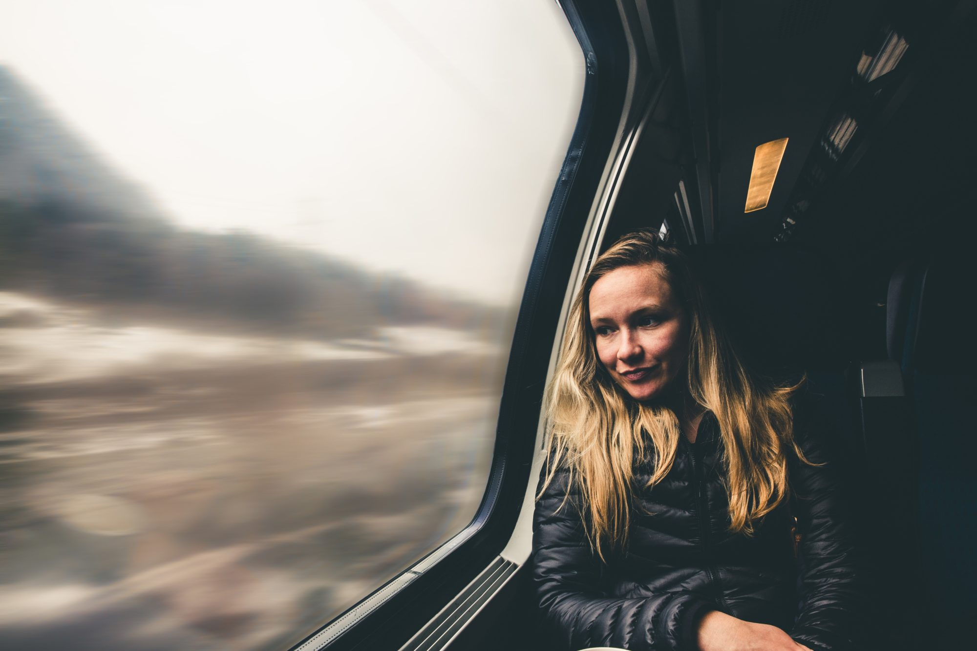 a woman looking out of a train window and a blurry landscape
