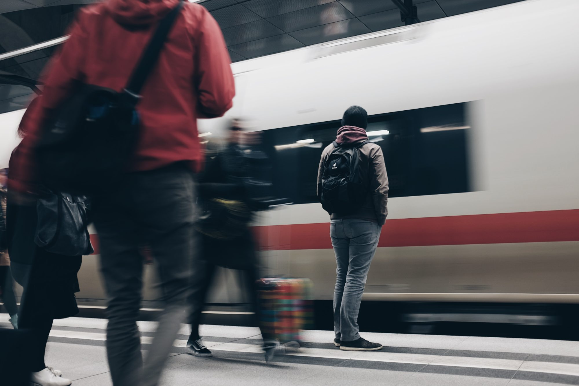 People on the move on a platform with a train entering