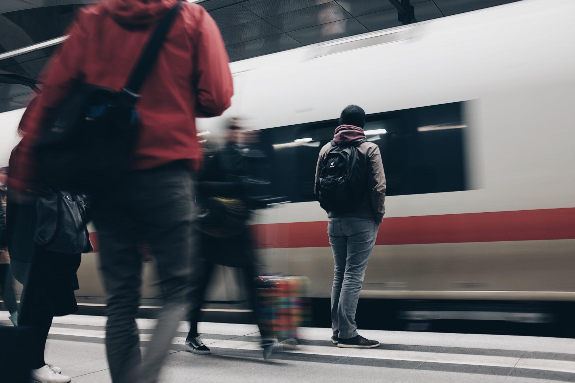 Menschen in Bewegung auf einem Bahnsteig mit einem einfahrenden Zug