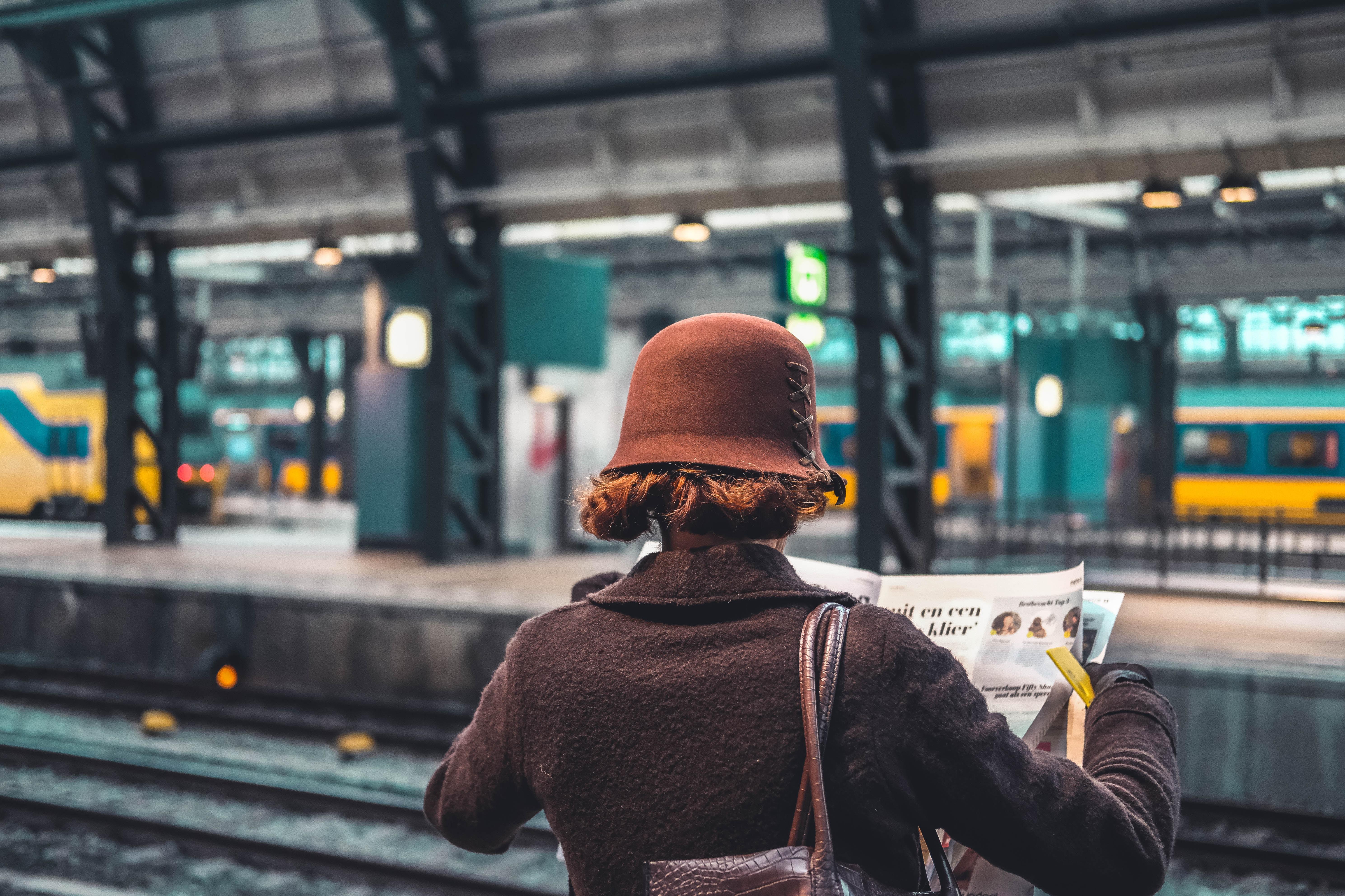 Bild von einer Zeitung lesenden Frau am Bahnsteig
