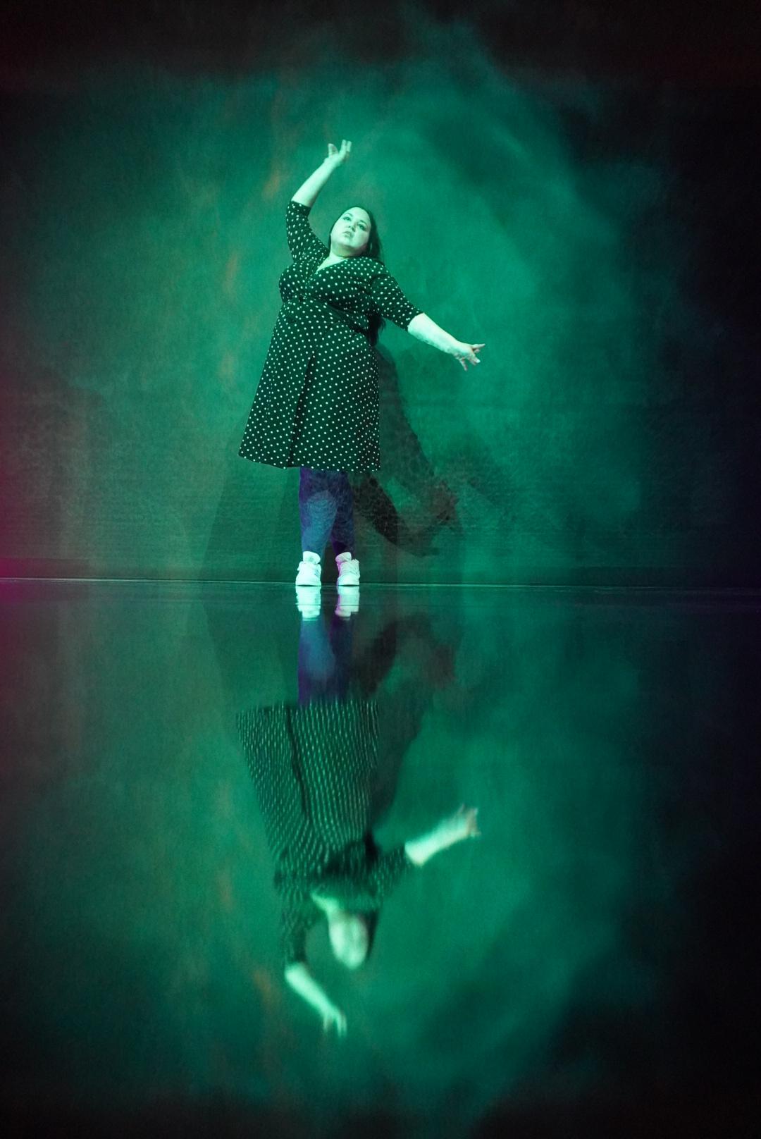 Auf dem Bild vom Museum of Popcorn in Hamburg Hafencity sieht man eine Frau in einem Kleid in einer Tanzpose. Das Bild ist in einen Grün Blau Ton getaucht, auch die Frau ist in das Licht getaucht, das wirkt, als wäre es Aquarellfarbe. An den Rändern ist es dunkel, durchbrochen von linken Lichtflecken ab und an.