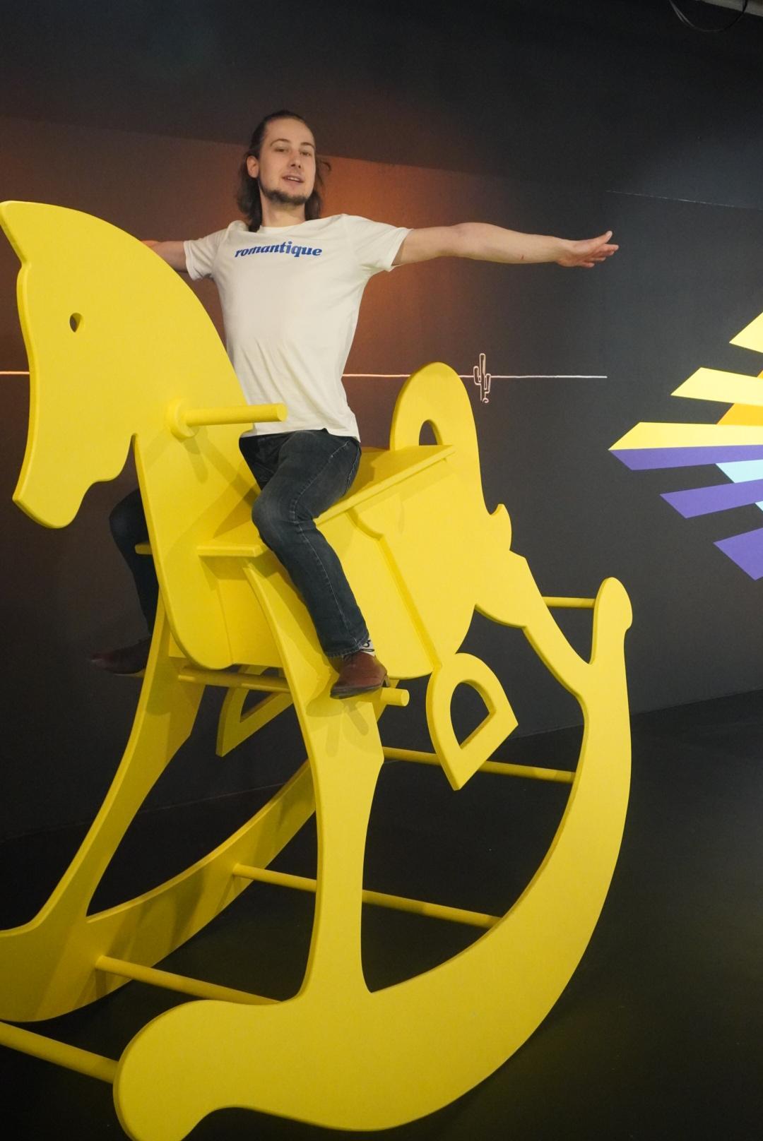 Im Museum of Popcorn in Hamburg Hafencity steht dieses gelbe übergroße Schaukelpferd. Auf dem Foto sieht man einen jungen Mann in weißen T-Shirt und Jeans auf dem Schaukelpferd freihändig balancieren. Der Hintergrund ist größtenteils schwarz.