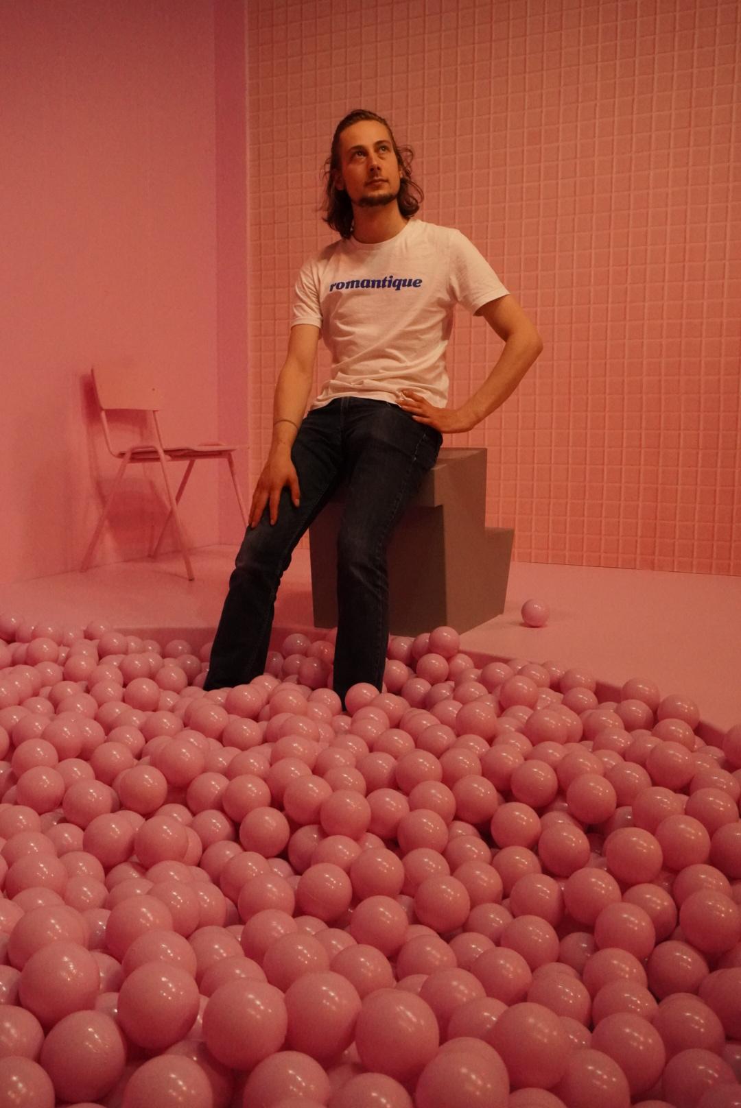 Auf dem Bild im Museum of Popcorn in Hamburg Hafencity sieht man einen jungen Mann in weißen T-Shirt und Jeans, der an die Decke blickt. Der Mann befindet sich in einem komplett rosafarbenen Raum. Im Vordergrund ist ein Bällebad, auf der linken Seite im Hintergrund steht ein Stuhl, links im Hintergrund eine blanke Wand, hinter ihm eine Kachelwand. Alles ist rosafarben. Nur der Springbock, auf dem der Mann sitzt, während seine Füße im Bällebad baumeln, ist in einem Grauton.