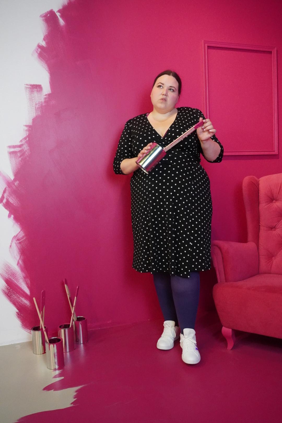 Auf dem Bild sieht man eine Frau in einem Punktkleid mit lila Strumpfhose und weißen Schuhen, die in einem komplett pinkfarbenen Raum steht, der an der linken Seite noch nicht fertig gestrichen ist. Unten auf dem Boden auf der linken Seite stehen einige silberne Farbdosen mit Pinseln drin. Die Frau hält eine der Dosen mit Pinsel in den Händen.