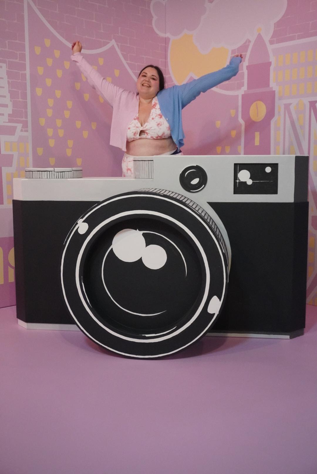 auf dem Bild im Museum of Popcorn in Hamburg Hafencity sieht man eine Frau in pastellfarbener Kleidung, die hinter eine übergroßen Kamera steht und ihre Arme ausstreckt und fröhlich lächelt. Sie trägt einen Sport BH in rosa und weiß von Fabletics in Batikoptik und man kann eine Ecke ihrer Hose in derselben Optik erkennen, der Rest ist von der übergroßen Kamera verdeckt. Im Hintergrund sieht man Wahrzeichen der Stadt Hamburg wie die Elbphilamonie in rosa, weiß und gelb.