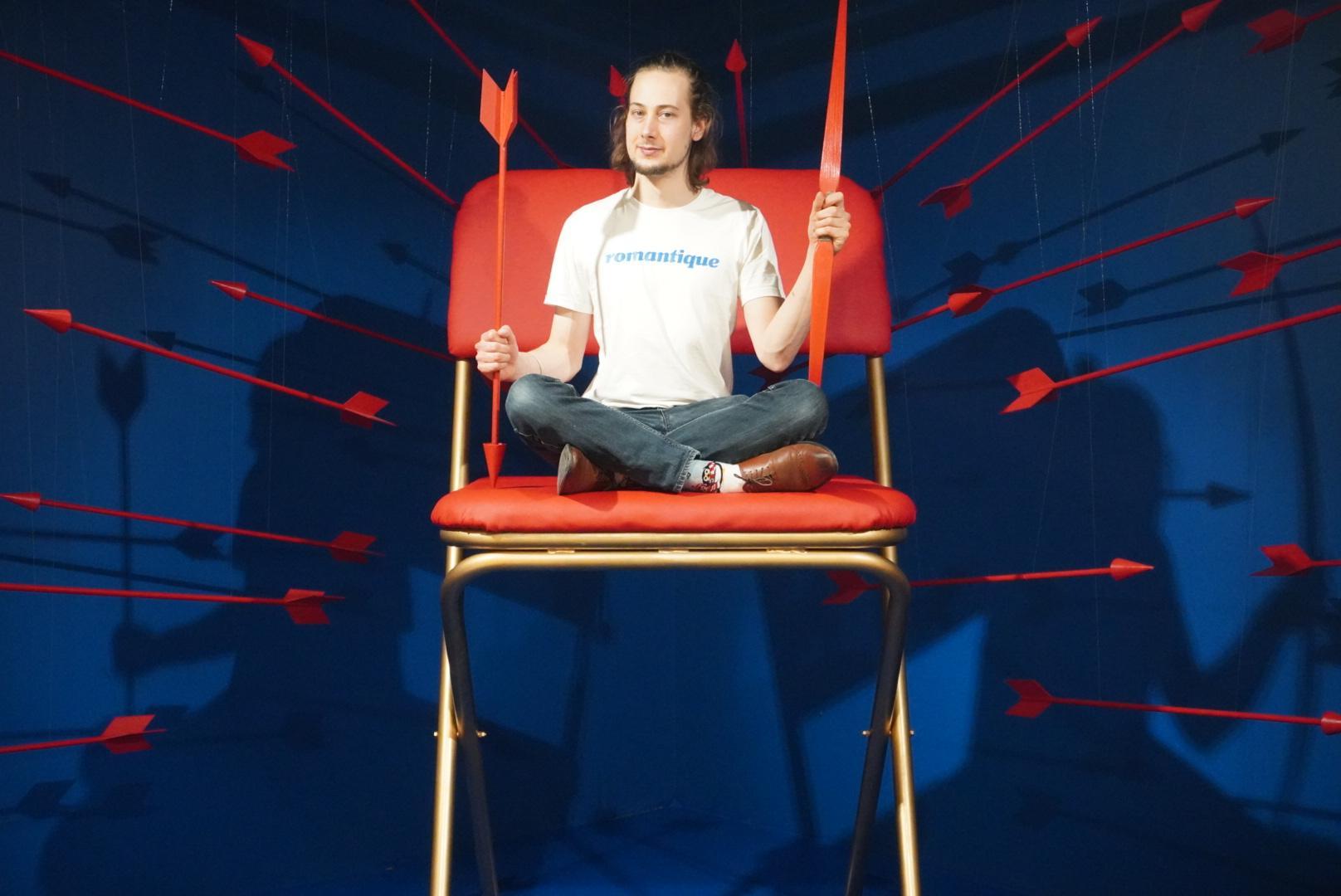 Auf dem Bild sieht man einen jungen Mann in weißen T-Shirt und Jeans in einer Bilderkulisse im Museum of Popcorn in Hamburg Hafencity. Im Bildzentrum steht ein übergroßer Klappstuhl in Rot und Silber, der junge Mann im Schneidersitz hält in der einen Hand einen roten Pfeil aus Holz und in der anderen Hand einen roten Bogen. Um ihn herum schweben viele rote Pfeile in der Luft vor dem blauen Hintergrund.